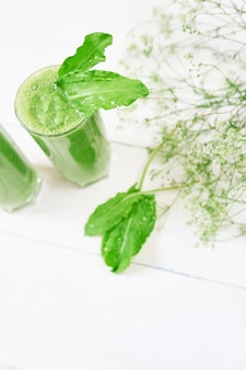 Blended green smoothie with ingredients or cocktail on white