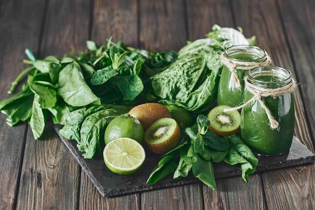 Смешанный зеленый смузи с ингредиентами на каменной доске, выборочный фокус на деревянном столе