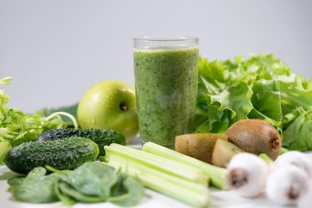 Смешанный зеленый смузи с ингредиентами на деревянном столе