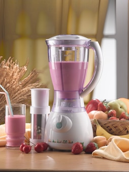 Blender and glass with smoothie inside