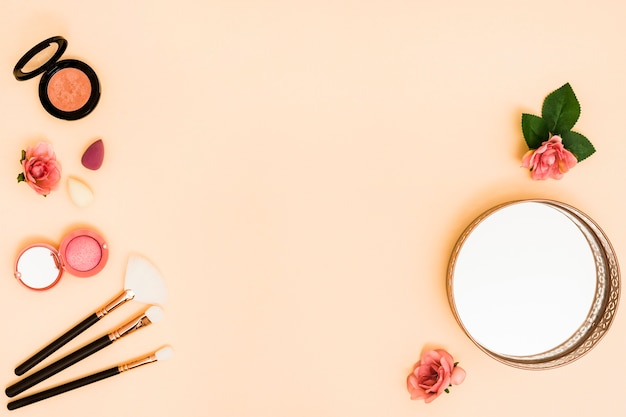 Blender; makeup brushes; rose; mirror and compact powder on beige background