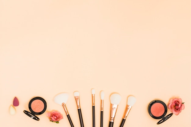 Blender; makeup brushes; roses; compact powder on beige background