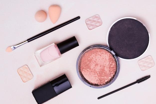 Blender sponge; makeup brush; eyeshadow; compact face powder on pink background