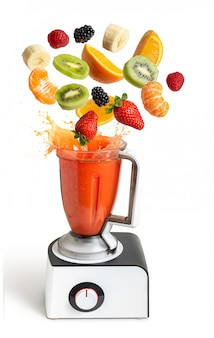 Blender with flying fruits on white isolated