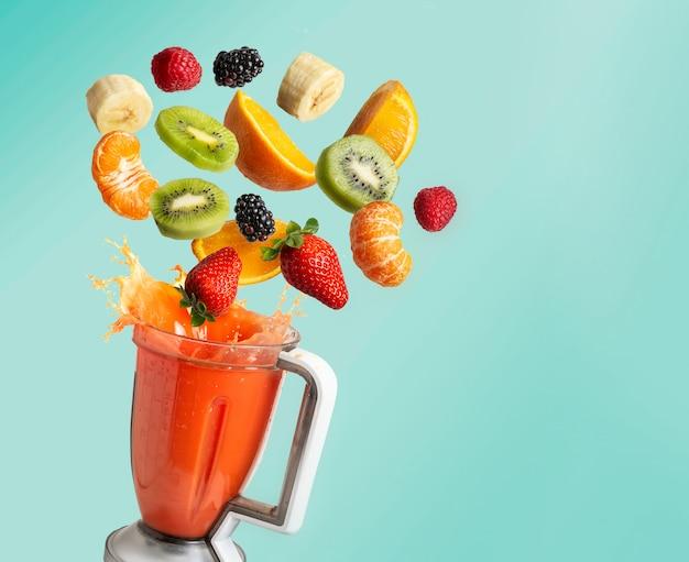 Блендер с фруктами, на синем фоне с копией пространства
