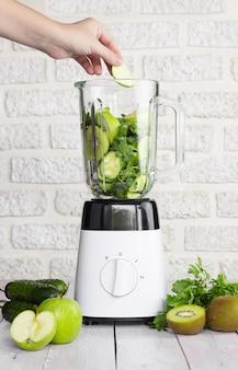 밝은 배경에 녹색 과일과 야채를 넣은 믹서기. 건강한 스무디의 준비. 손은 믹서기 그릇에 사과 조각을 넣습니다.