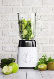 밝은 배경에 녹색 과일과 야채를 넣은 믹서기. 건강한 스무디의 준비.