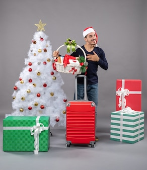 Blessed young man with santa hat holding gift basket with both hands near xmas tree on grey