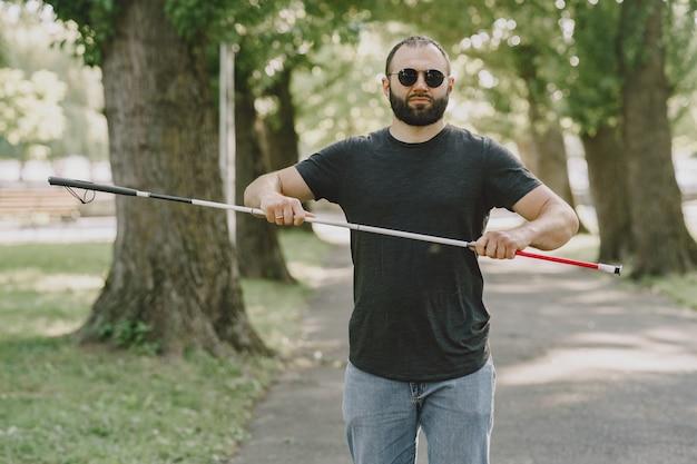 盲目の男。障害者、障害者、日常生活。都市公園の階段を降りて、杖を持つ視覚障害者。