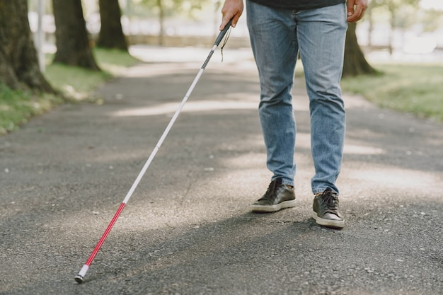Слепой человек. люди с ограниченными возможностями, инвалиды и повседневная жизнь. слабовидящий мужчина с тростью, спускается по ступеням в городском парке.