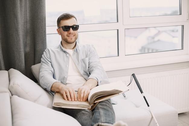 ソファで点字の本を読んでいる盲人。障がい者