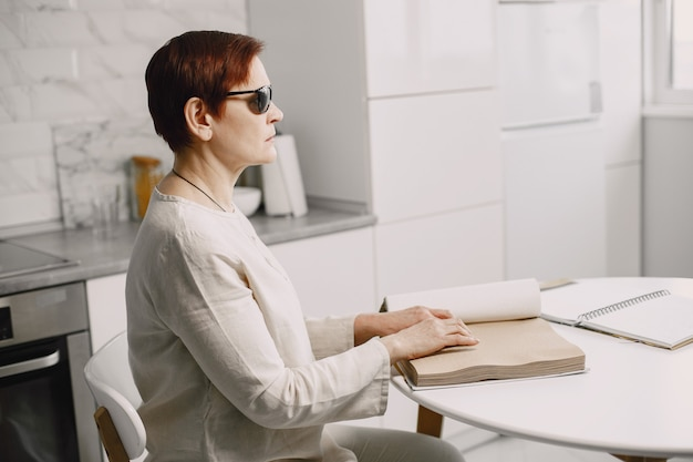 Blind mature woman reading braille book at home Premium Photo