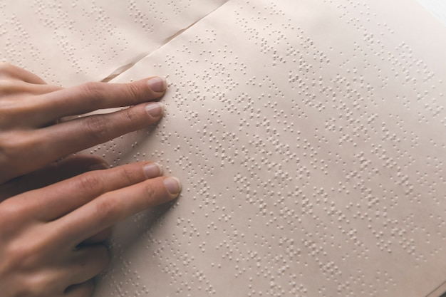 Blind person reads the text of a braille book