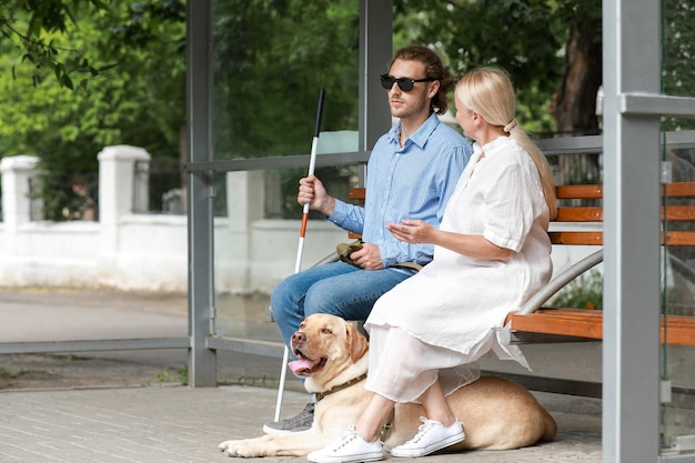 Blind young man with guide dog and mother waiting for bus outdoors
