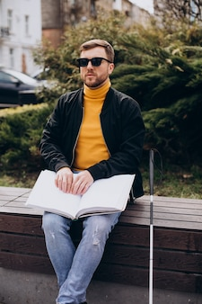 Blinded man reading by touching braille book