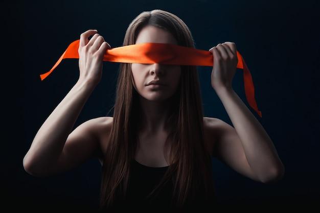 Девушка с завязанными глазами на темном фоне