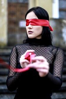 赤いリボンで目隠しされた女の子