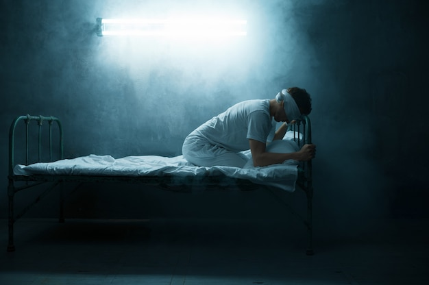 Психо-мужчина с завязанными глазами сидит в постели, ужас бессонницы, темная комната .. психоделический человек мужского пола, имеющий проблемы каждую ночь, депрессия и стресс, грусть