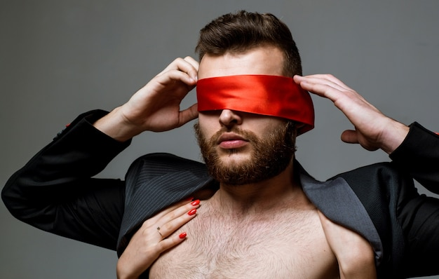 Blindfolded. woman covering man eyes. sexy girl closes eyes of a man