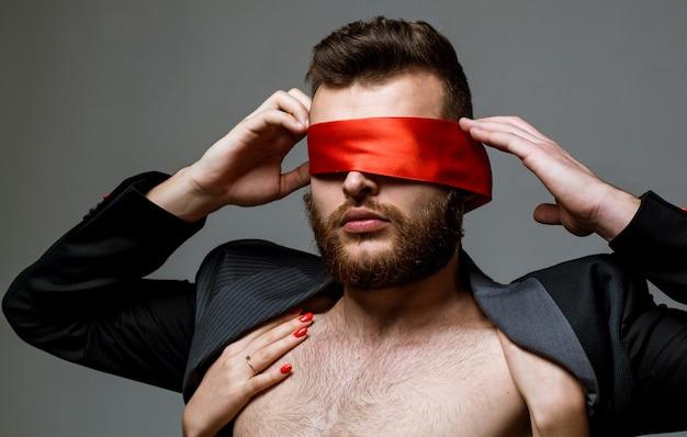 눈가리개. 남자 눈을 다루는 여자. 섹시한 여자는 남자의 눈을 닫습니다