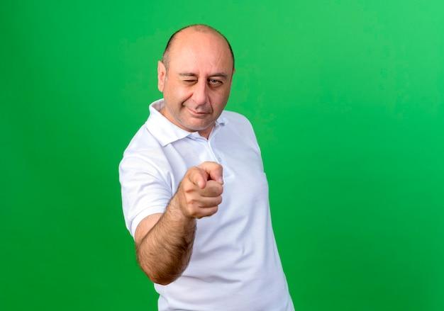 깜박이 캐주얼 성숙한 남자 포인트 복사 공간이 녹색 벽에 고립