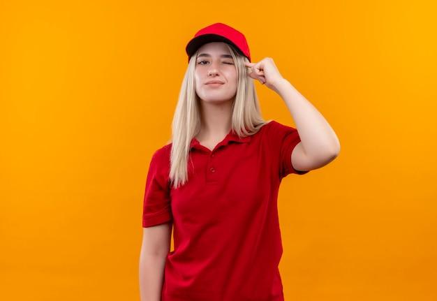 La giovane donna di consegna sbattuta che indossa la maglietta e il cappuccio rossi ha messo il suo dito sulla testa sulla parete arancione isolata