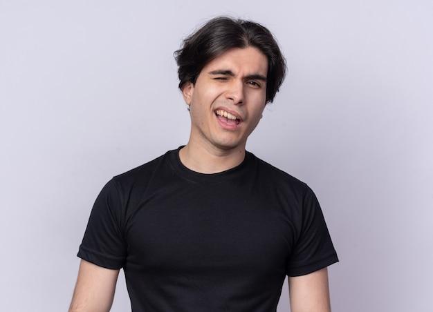 白い壁に分離された黒いtシャツを着て正面の若いハンサムな男を見て点滅