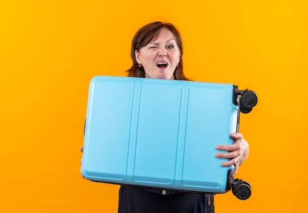 Моргнула женщина-путешественница средних лет, держащая чемодан на изолированной желтой стене