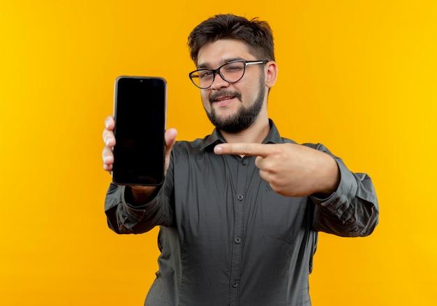 노란색 배경에 고립 된 전화에서 안경 들고 포인트를 입고 깜박이 기쁘게 젊은 사업가