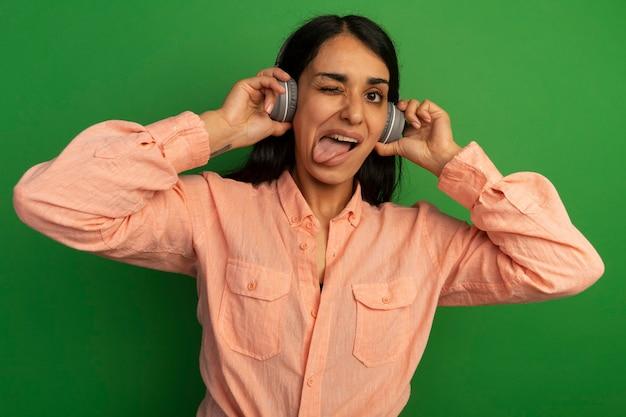 녹색 벽에 고립 된 혀를 보여주는 헤드폰으로 분홍색 티셔츠를 입고 깜박이 젊은 아름 다운 소녀