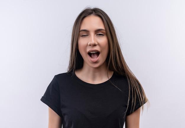 Моргнула молодая кавказская девушка в черной футболке на изолированной белой стене