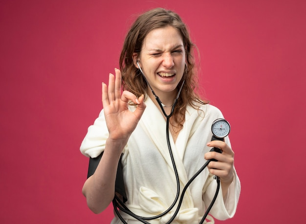 Моргнула молодая больная девушка в белом халате, измеряющая собственное давление с помощью сфигмоманометра, показывающая нормальный жест, изолированный на розовом