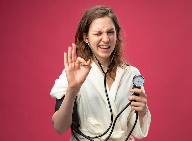 Sbatté le palpebre giovane ragazza malata che indossa una veste bianca che misura la propria pressione con sfigmomanometro che mostra il gesto giusto isolato sul rosa