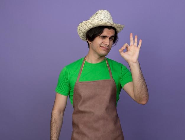 大丈夫なジェスチャーを示すガーデニング帽子をかぶった制服を着た若い男性の庭師の点滅