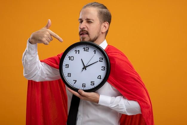 Sbatté le palpebre il giovane supereroe che indossava la cravatta e indica l'orologio da parete isolato sull'arancio