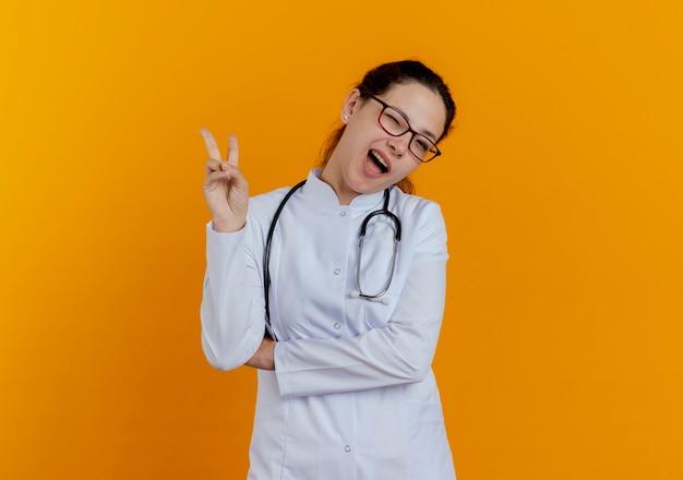 Мигающая молодая женщина-врач в медицинском халате и стетоскоп в очках, показывающая жест мира изолированы