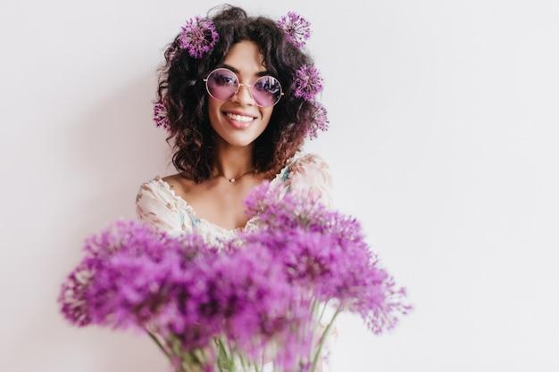 美しい花束でポーズをとって笑っている至福のアフリカの女の子。孤立した明るいブルネットの女性の屋内ショット。