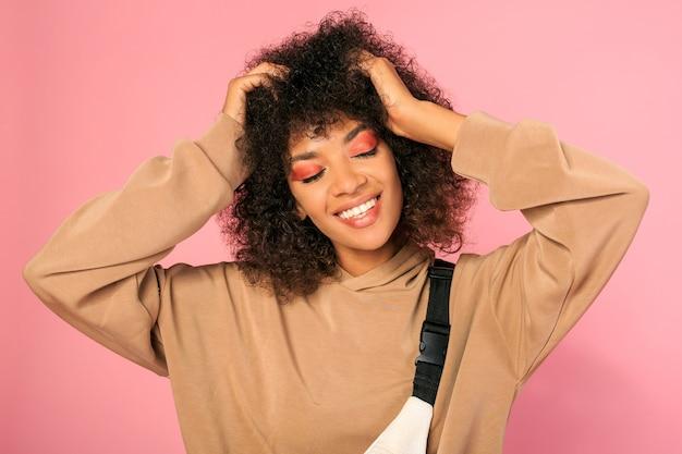 Блаженная африканская женщина с ярким макияжем позирует на розовом