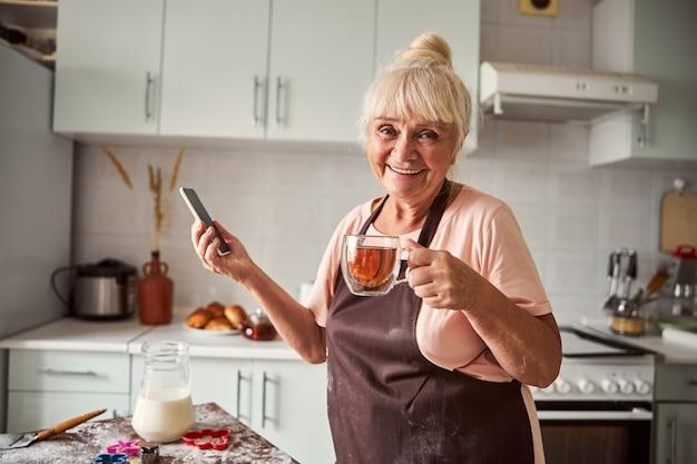 가족에게 전화하기 위해 차를 마시는 행복한 노부인