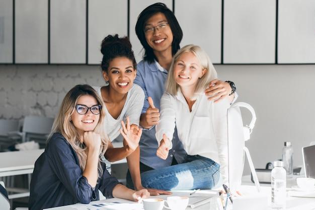 写真と笑顔のために女性の金髪の同僚を抱きしめる至福のアジアのプログラマー。彼女の職場でヨーロッパの友人の横にポーズをとってうれしいアフリカのサラリーマンの屋内の肖像画。