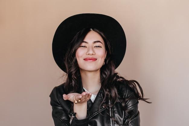 ベージュの背景に身振りで示す帽子の至福のアジアの女性。革のジャケットでロマンチックな巻き毛の日本人女性のスタジオショット。
