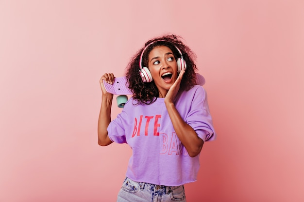 스케이트 보드와 함께 포즈 곱슬 헤어 스타일으로 행복 한 흑인 소녀. 음악을 듣고 캐주얼 옷에 좋은 기분 좋은 아프리카 여성 모델.