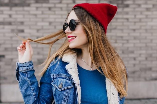 야외 사진 촬영 중에 멀리 찾고 트렌디 한 데님 재킷에 행복 한 금발 소녀. 벽돌 벽에 그녀의 스트레이트 헤어와 함께 연주 선글라스에 매력적인 백인 아가씨의 사진.