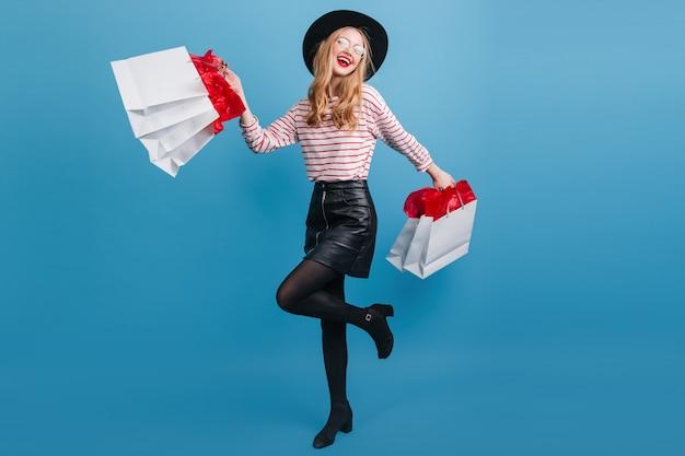 Beata ragazza bionda in gonna di pelle che balla sulla parete blu. gioiosa giovane donna con le borse della spesa.