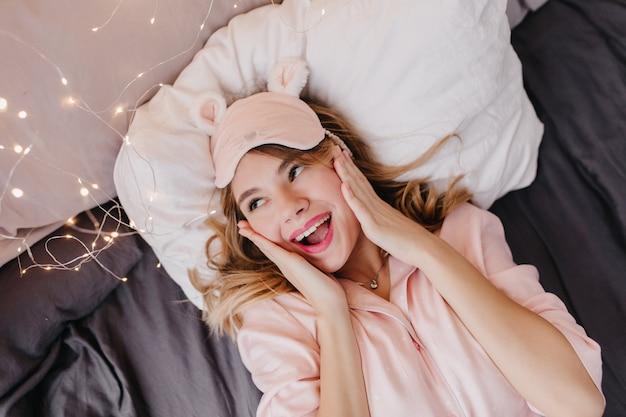 驚きの笑顔でベッドでポーズをとる至福のブロンドの女の子。ポジティブな感情を表現するパジャマとアイマスクで幸せな女性の屋内の肖像画。