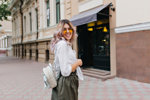 Blissful blonde girl in white shirt and dark skirt walking with elegant backpack on the street and laughing