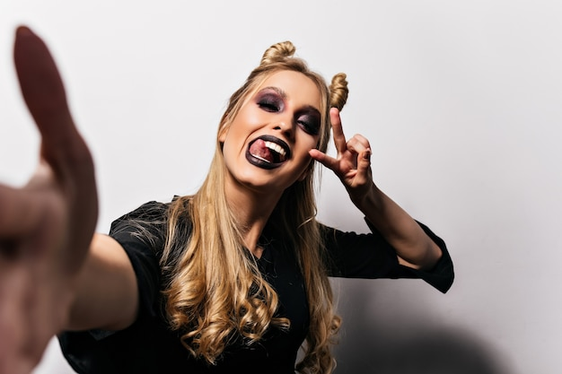 Blissful blonde girl with black lips making selfie in halloween. amazing young witch funny posing on white wall.