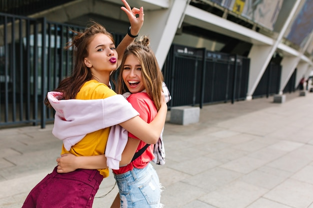 Blissful brown-haired girl in trendy purple shorts posing with peace sign and kissing face expression hugging friend