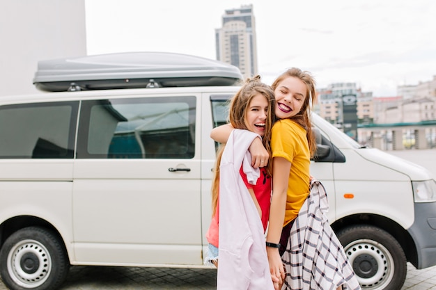 Beata ragazza dai capelli castani con un sorriso felice che abbraccia la sua migliore amica con l'acconciatura alla moda