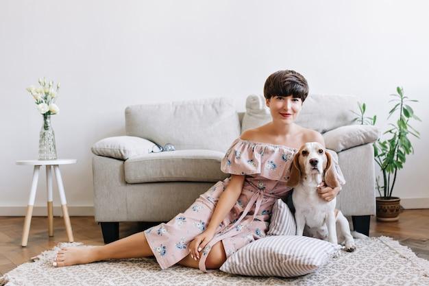 Beata ragazza bruna in abito carino si siede sul tappeto davanti al divano grigio con il suo cucciolo